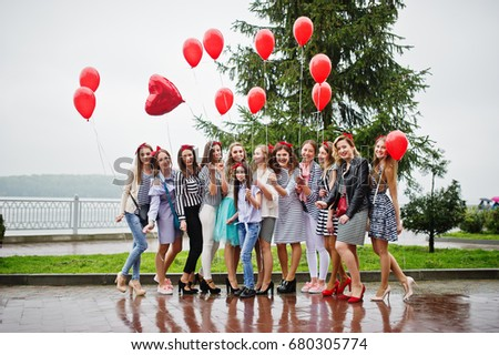 Eleven amazingly-looking braidsmaids with stunning bride posing with red heart-shaped balloons on the pavement against the lake in the background. #680305774