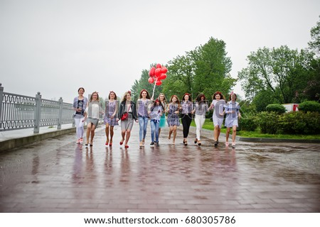 Eleven amazingly-looking braidsmaids with stunning bride posing with red heart-shaped balloons on the pavement against the lake in the background. #680305786