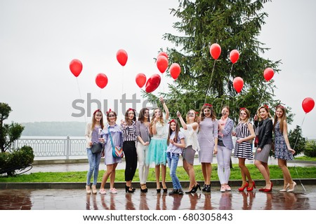 Eleven amazingly-looking braidsmaids with stunning bride posing with red heart-shaped balloons on the pavement against the lake in the background. #680305843