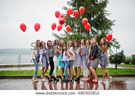 Eleven amazingly-looking braidsmaids with stunning bride posing with red heart-shaped balloons on the pavement against the lake in the background. #680305852