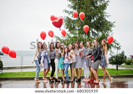 Eleven amazingly-looking braidsmaids with stunning bride posing with red heart-shaped balloons on the pavement against the lake in the background. #680305939