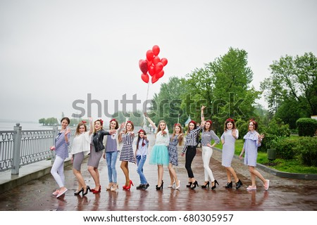 Eleven amazingly-looking braidsmaids with stunning bride posing with red heart-shaped balloons on the pavement against the lake in the background. #680305957