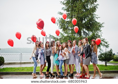 Eleven amazingly-looking braidsmaids with stunning bride posing with red heart-shaped balloons on the pavement against the lake in the background. #680305963