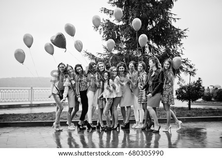 Eleven amazingly-looking braidsmaids with stunning bride posing with red heart-shaped balloons on the pavement against the lake in the background. Black and white photo. #680305990