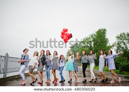 Eleven amazingly-looking braidsmaids with stunning bride posing with red heart-shaped balloons on the pavement against the lake in the background. #680306020