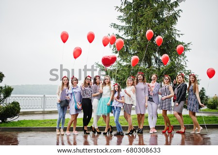Eleven amazingly-looking braidsmaids with stunning bride posing with red heart-shaped balloons on the pavement against the lake in the background. #680308633