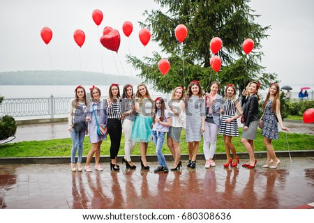 Eleven amazingly-looking braidsmaids with stunning bride posing with red heart-shaped balloons on the pavement against the lake in the background. #680308636