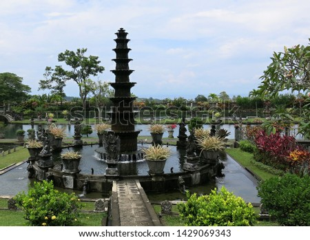 Eleven-levelsfountain in the water palace. Promenade in tropical garden. Tropical garden with palm and many colorful flowers. Water tank with koi carp. Sunny day. Sunlit tropical garden. #1429069343