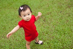 Eleven month old Asian baby girl wearing red romper standing on green grass