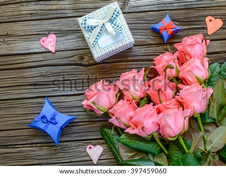 Eleven pretty stemmed pink roses and little three little Valentines gift boxes next to heart shapes over old wood background with copy space #397459060