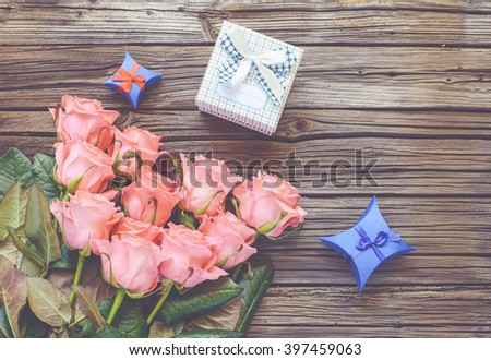 Eleven pretty stemmed pink roses and little three little Valentines gift boxes next to heart shapes over old wood background with copy space #397459063