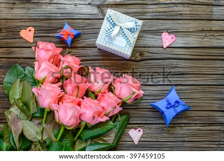 Eleven pretty stemmed pink roses and little three little Valentines gift boxes next to heart shapes over old wood background with copy space #397459105