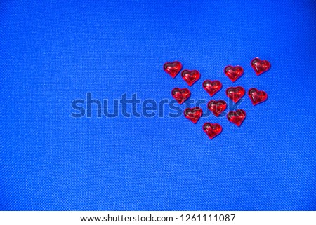 Eleven red glass hearts on a blue background. Valentine's Day. #1261111087
