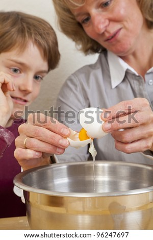 eleven years old boy watching his mother separating egg white from egg yolk