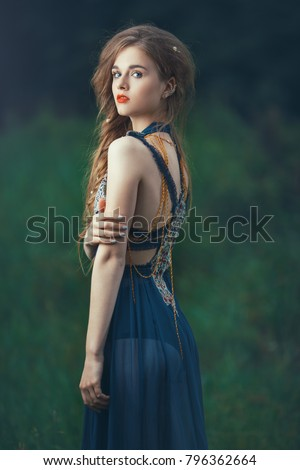 Elf. Beautiful girl in magic forest. Fantasy young woman in woods outdoors at night. Creative portrait of young model in fantastic costume. Side view.