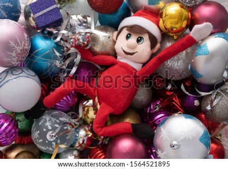 Elf on the shelf being naughty playing in a ball pond of christmas baubles. Cute tradition of sending Santa's elf to check up on children just before christmas.