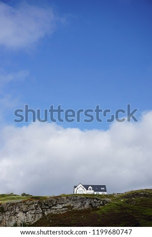ELGON, SCOTLAND. AUGUST, 2018: White house with black tiled roof surrounded by clouds in the top of a green hill in Scotland in the island of Skye.                    #1199680747
