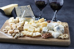 Elite cheeses: with truffle, dor blue, brie, parmesan and assortment of nuts on a wooden board. Appetizer for a wine party. Close up