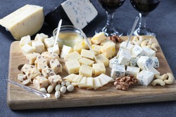 Elite cheeses: with truffle, dor blue, brie, parmesan and assortment of nuts on a wooden board on gray background. Wine party snack.