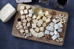 Elite cheeses: with truffle, dor blue, brie, parmesan and assortment of nuts on a wooden board on gray background. Wine party snack. View from above