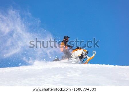 elite sports snowmobiler rides and jumps on steep mountain slope with swirls of snow storm. background of blue sky leaving a trail of splashes of white snow. bright snowmobile and suit without brands Сток-фото ©