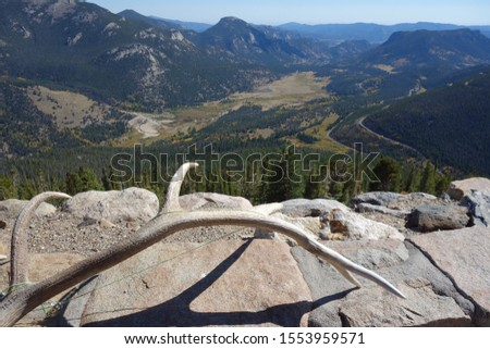 elk antler on a stone wall with a mountain view #1553959571