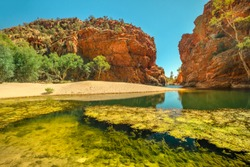 Ellery Creek Big Hole, a waterhole in a gorge surrounded by high red cliffs, is one of most popular camping, walking, swimming spots in West MacDonnell National Park, Northern Territory, Australia.