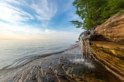 Elliot Falls spills over sculpted rock at Pictured Rocks National Lakeshore in Munising Michigan. This little waterfall is on Miner's Beach and sunrise skies light the background