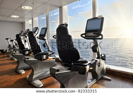 elliptical cross trainer in a row in a gym on a cruise liner with a view to the ocean
