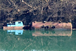 Elongated large rusted storage tank with old car tyres used as protection bumpers next to vintage retro old partially rusted river barge converted in creepy small metal river boat enclosed with metal