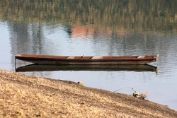 Elongated old dilapidated light brown wooden river boat made from wooden boards left tied with rusted chain next to dry grass covered river bank on warm sunny winter day