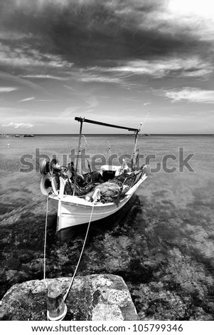 Els Pujols beach in Formentera with traditional fishing boat in black and white - stock photo