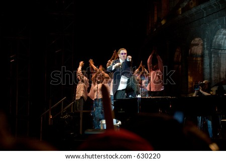 Elton John standing on the piano and gospel singers at live in Rome on 3rd of september 2005