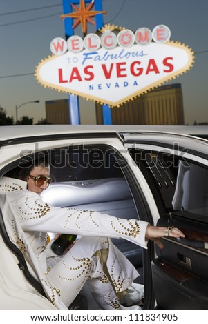 Elvis impersonator in the car in front of a 'Welcome to Las Vegas' sign - stock photo