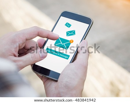 Email app on smartphone screen. You receive a message, New message is received. Man's Hand holding a smartphone #483841942
