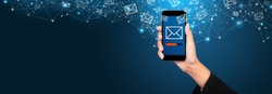 Email marketing and newsletter concept. Sending a message on smartphone screen in businesswoman hand.