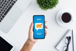Email marketing and newsletter concept. Top view of unrecognizable young woman holding modern mobile phone with new mail notification on screen, creative collage