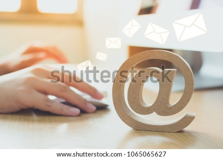 Email marketing concept, Hand using computer sending message with wooden email address symbol and envelope icon