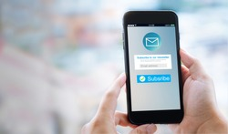 Email marketing subscribe our newsletter concept.Female hands using mobile phone with copyspace