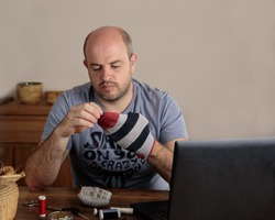 Emancipated man darning his socks in the kitchen of his home. On the table are a laptop computer and sewing supplies. Copy space.