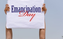 Emancipation Day banner in hand in sky background