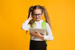 Embarassed Primary School Student Girl Scratching Head Using Digital Tablet On Yellow Background. Studio Shot, Empty Space