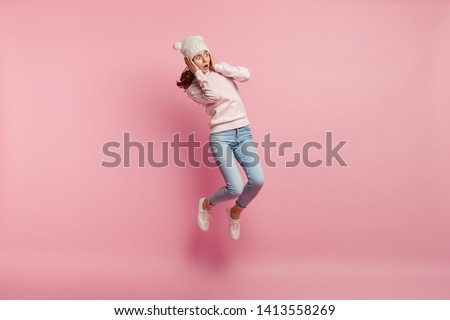 Embarrassed frightened young woman covers ears, jumps high in air, focused aside with bugged eyes, ignores loud noise, dressed in stylish clothes, isolated over pink background. Omg concept.