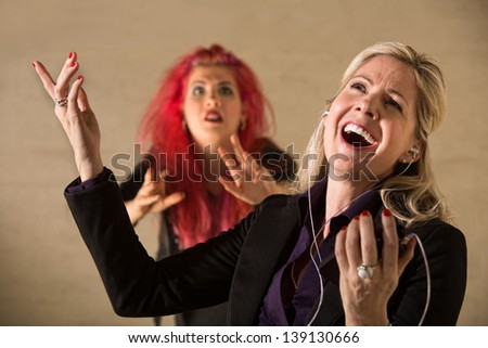 Embarrassed teen in pink hair with singing parent holding mp3 device #139130666