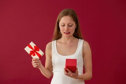 Embarrassed woman looking on a present on red background Dissappointed female with box in hands. Blonde girl confused by valentine gift.