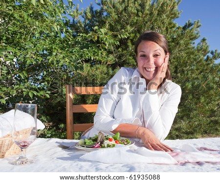 Embarrassed woman trying to cover wine that she spilled on white table cloth