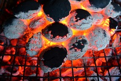 Ember on grill, pile of burning coal under and on grill, preparation for barbeque almost done, horizontal orientation, close up view