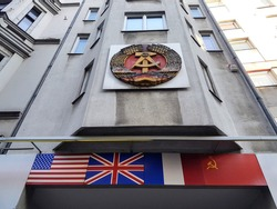 Emblem of East Germany fixed onto a building above the four flags of the nations occupying Germany after World War II, By Checkpoint Charlie, Berlin, February 2020