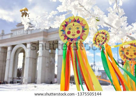 emblem of sun with colorful ribbons on branches of white tree,multi-colored ribbons against stone building,sun picture,Shrovetide in park,images of sun with ribbons at Shrovetidel,Pancake week