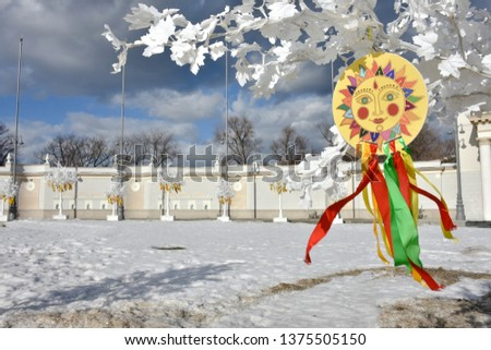 emblem of sun with colorful ribbons on branches of white tree,the symbol of carnival on white tree in the park,sun picture,Shrovetide in park,images of the sun with ribbons at Shrovetidel,Pancake week